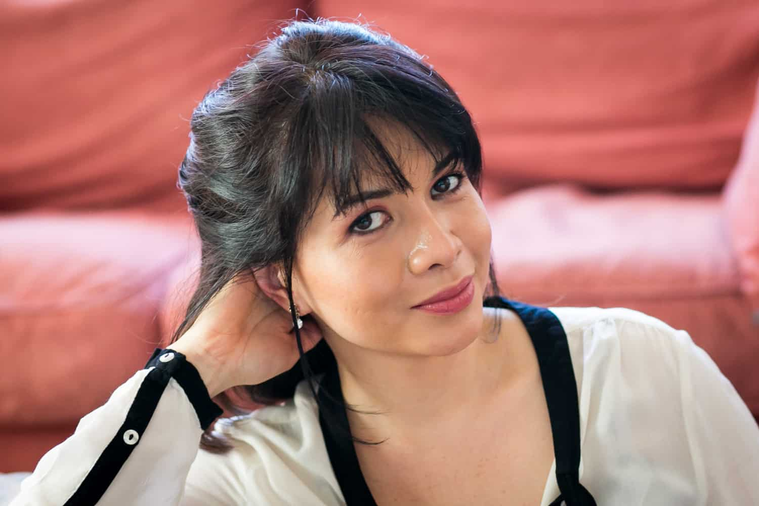 Woman with short black hair wearing black and white blouse