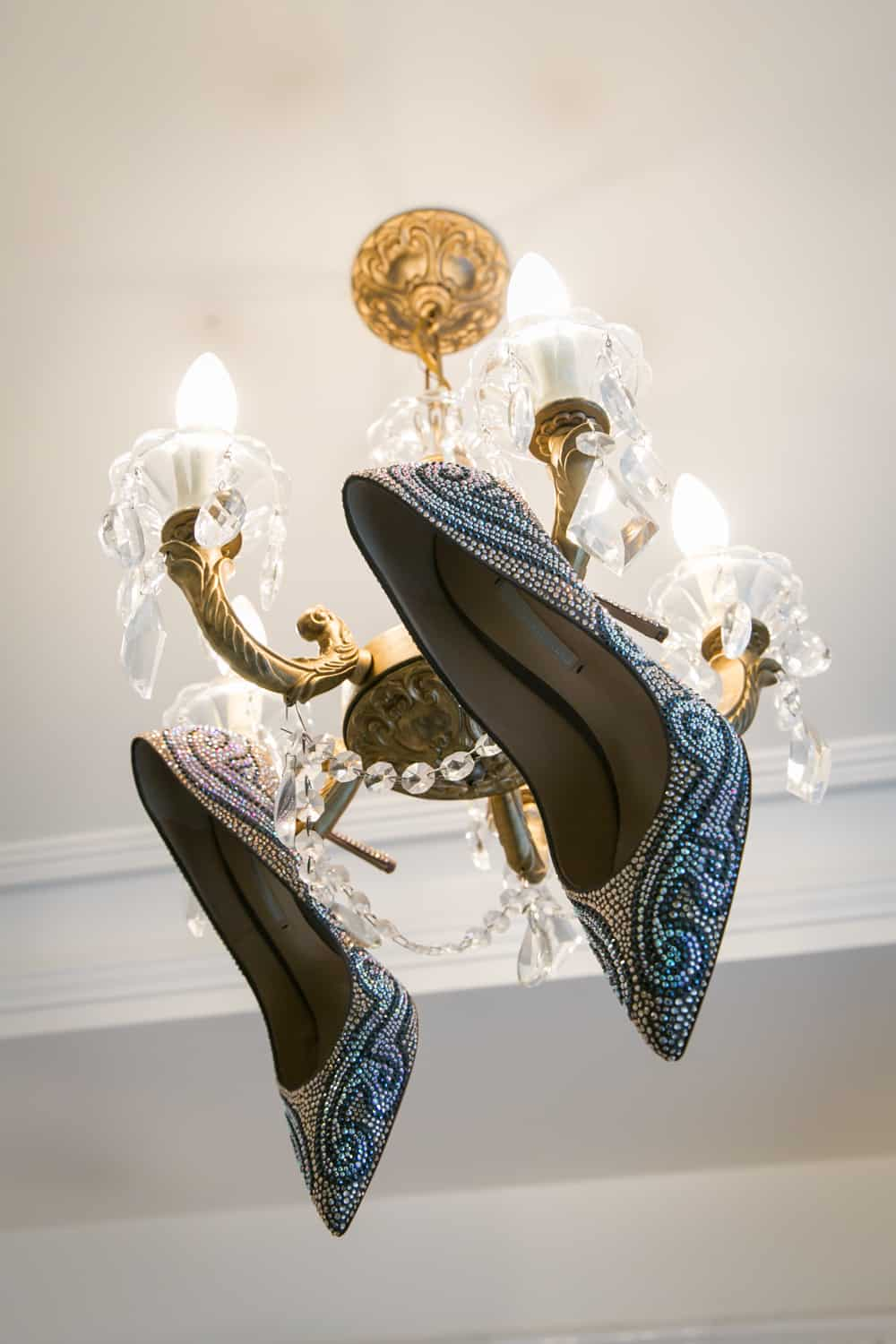 Sequined high heels hanging off a chandelier