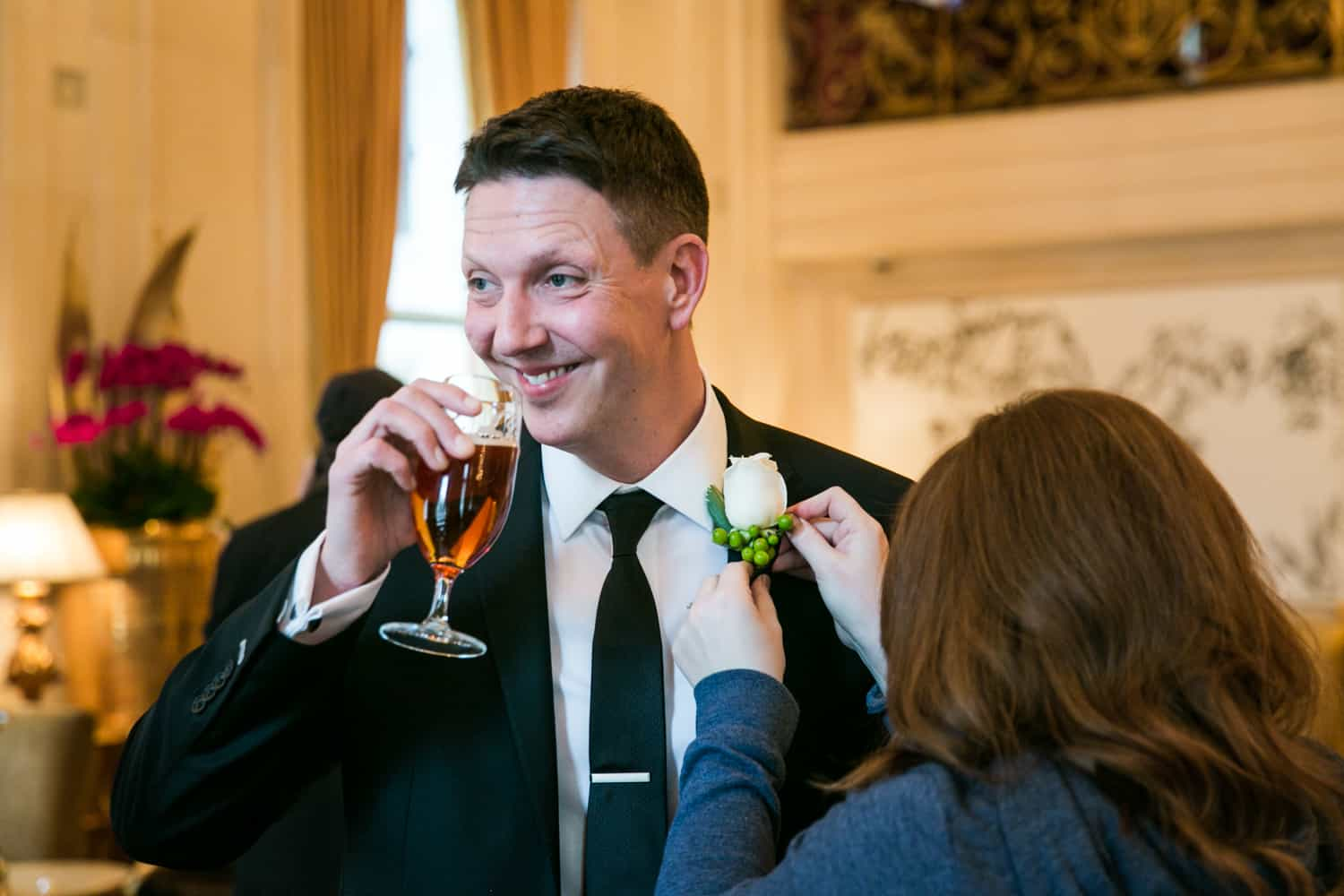 Groom drinking glass of beer while having boutonniere put on