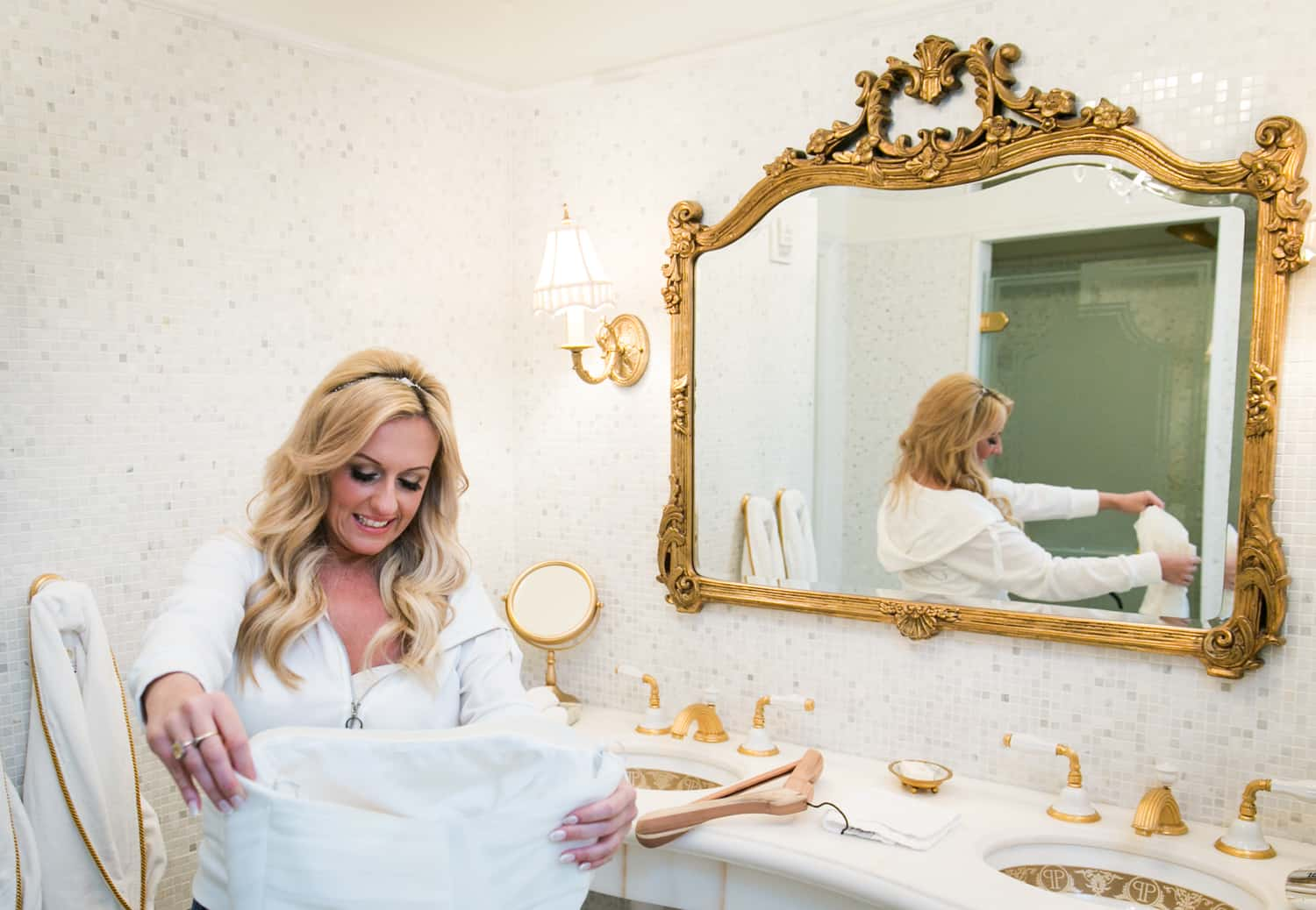 Bride looking at wedding dress in bathroom