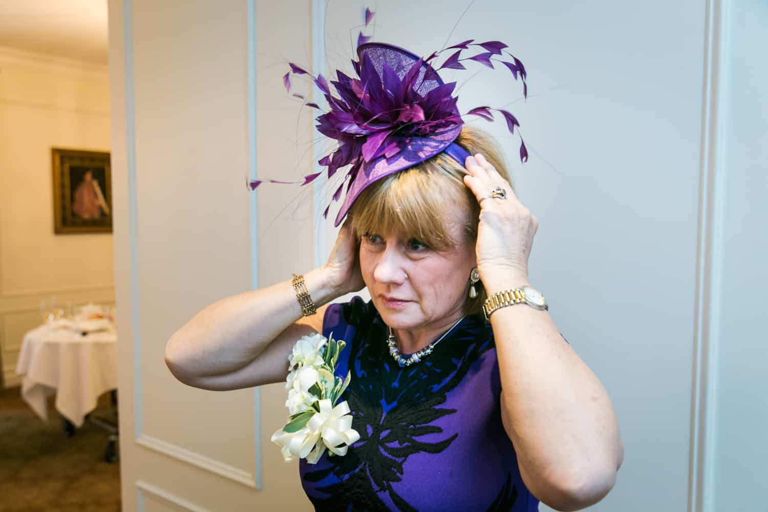 Woman adjusting purple hat before wedding