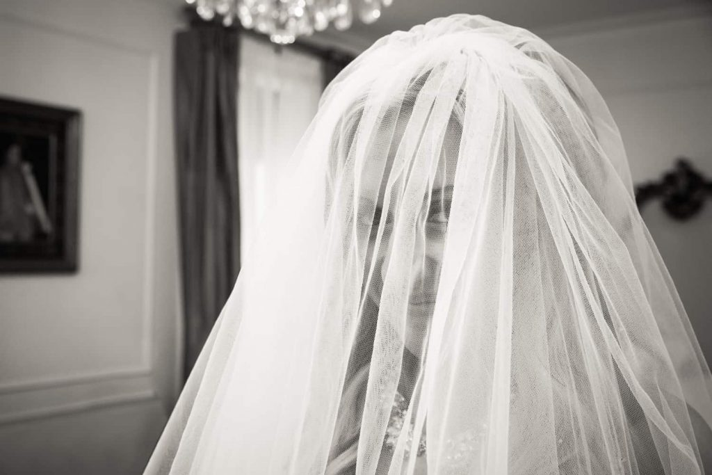 Black and white photo of bride looking through veil