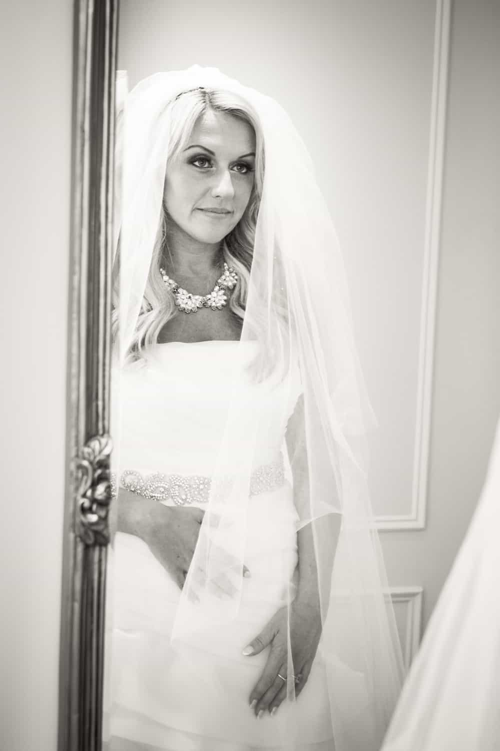 Black and white photo of bride looking at herself in mirror