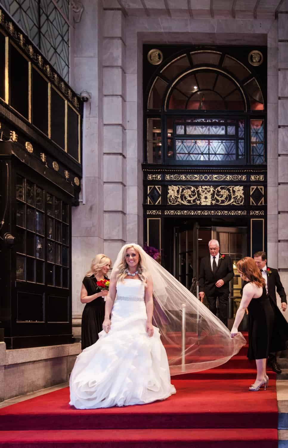 Bride walking down stairs of Plaza Hotel before wedding