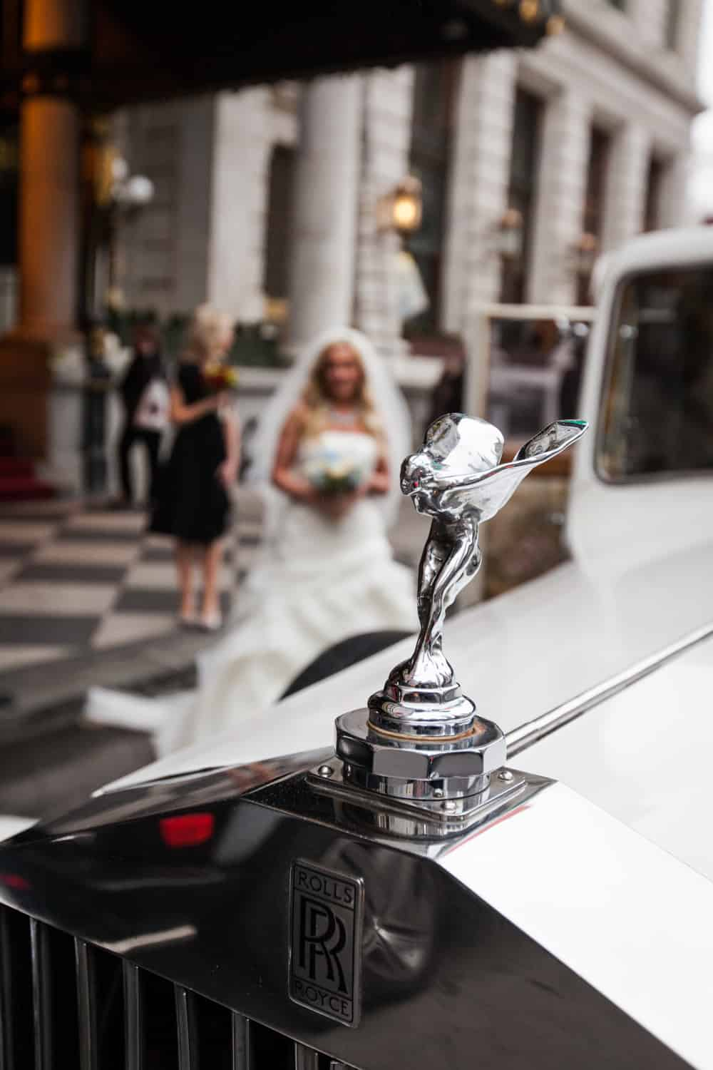 Rolls Royce car mascot with bride in background