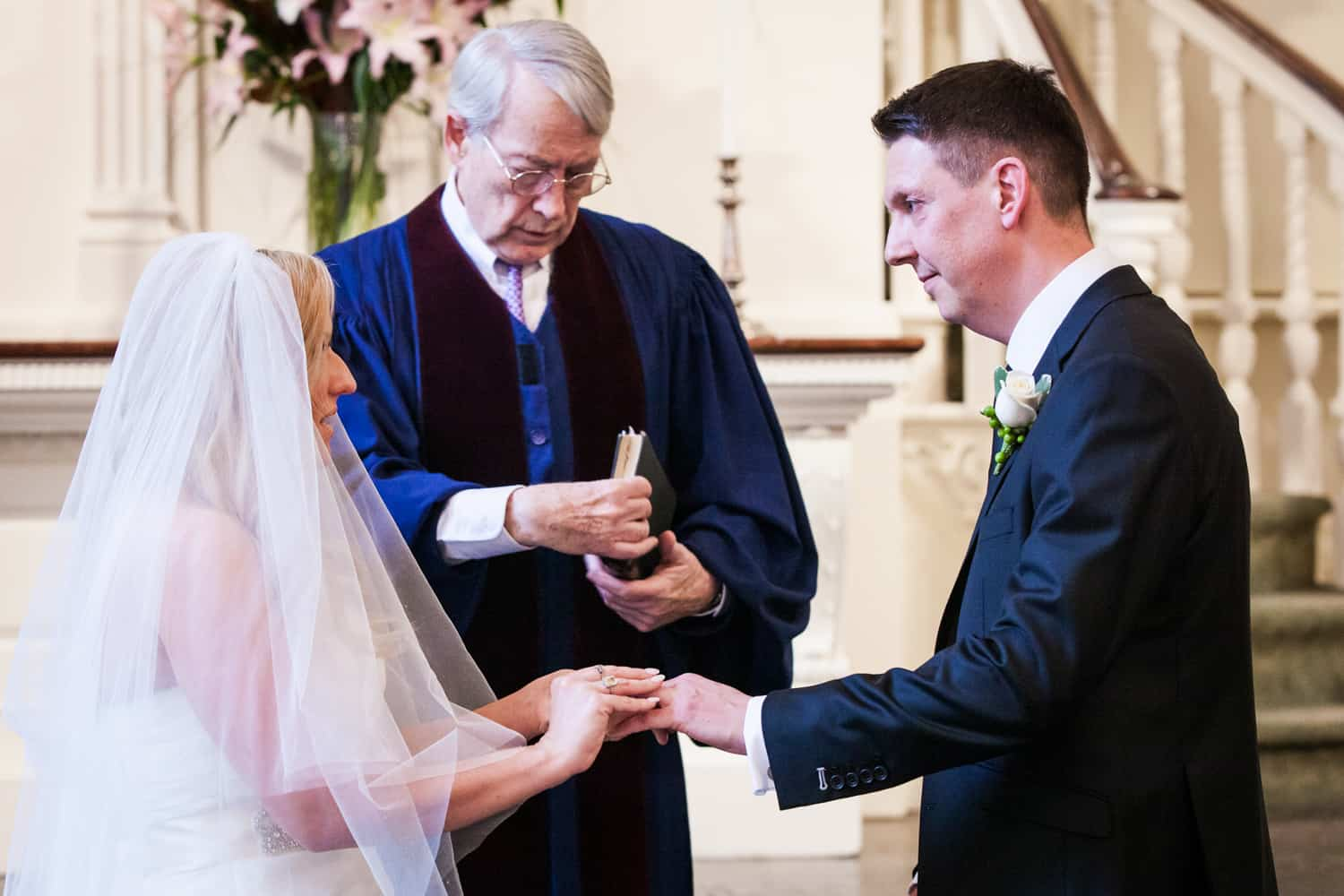Bride putting ring on groom's finger during All Souls Unitarian Church ceremony