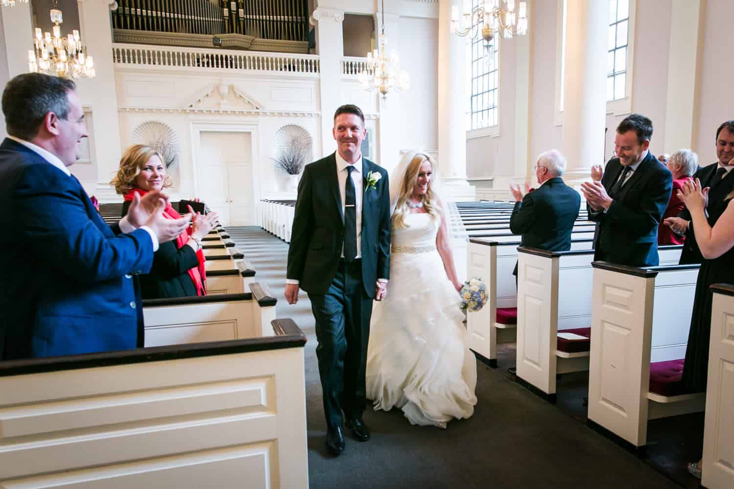 Bride and groom greeting guests during All Souls Unitarian Church ceremony
