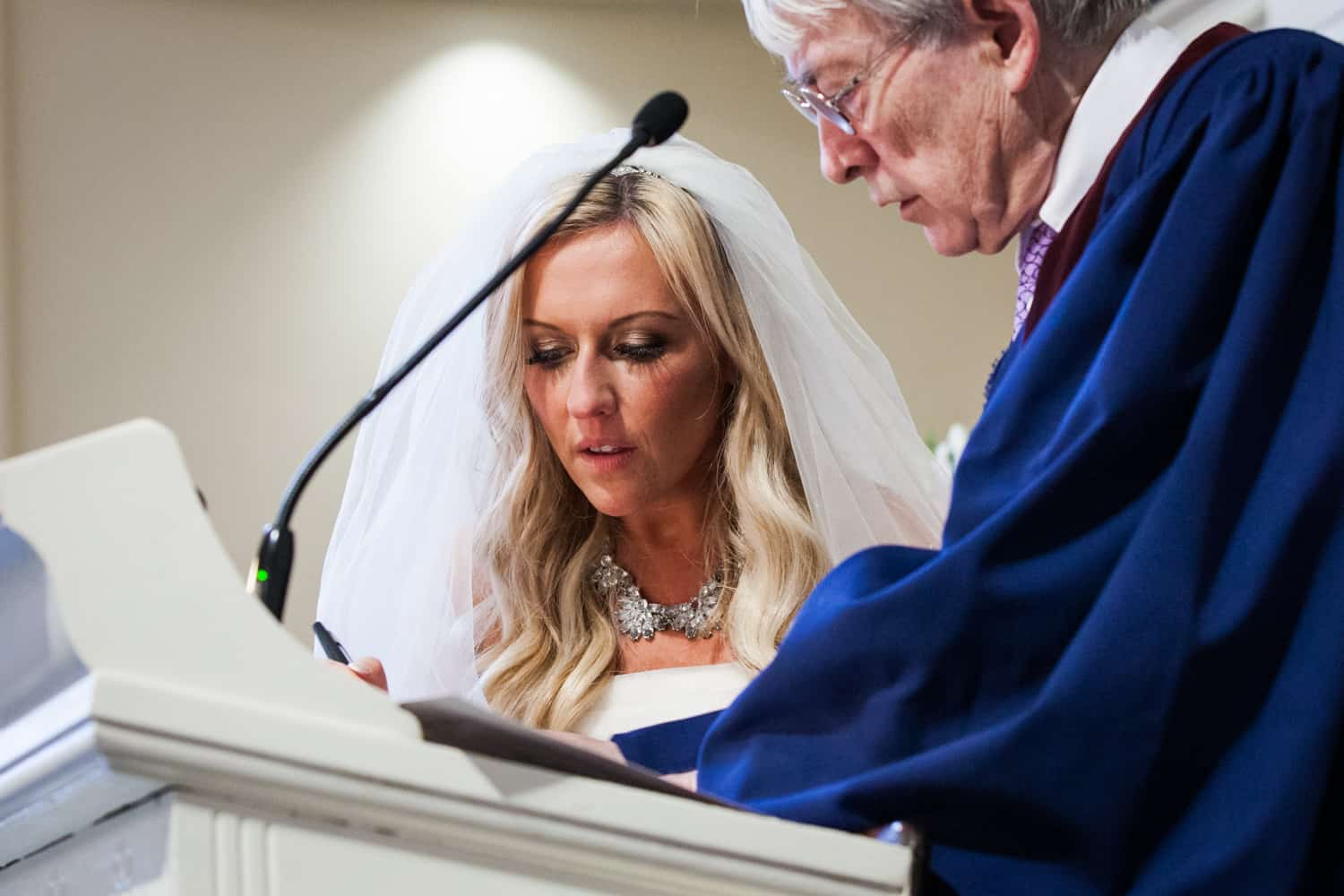 Bride signing marriage license with pastor