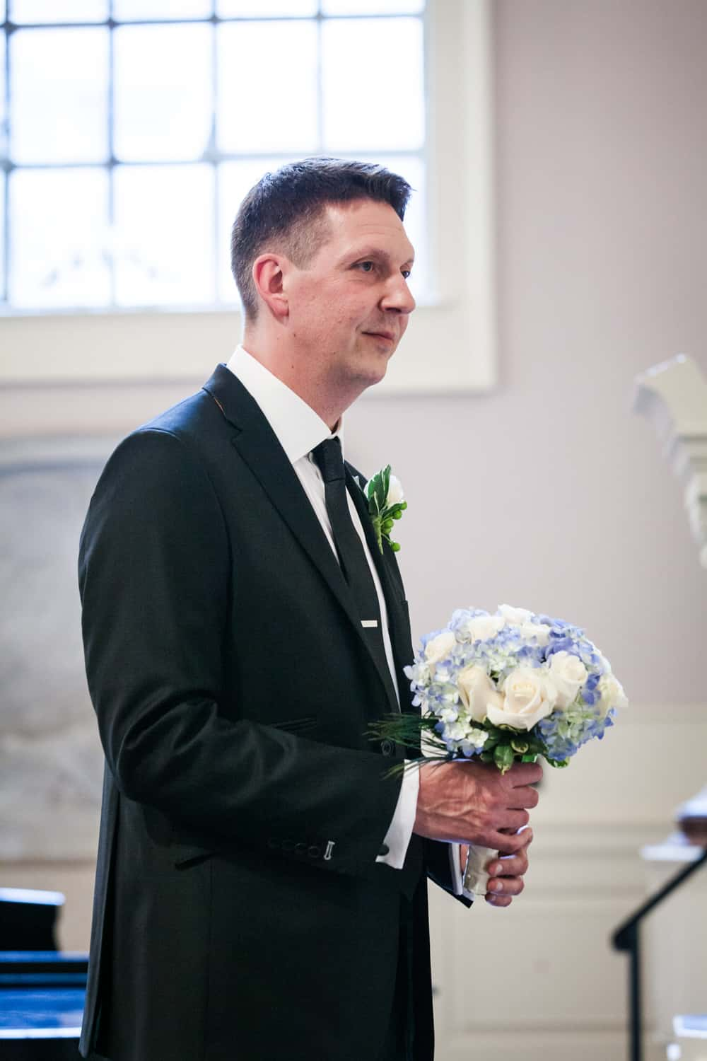 Groom holding bride's bouquet