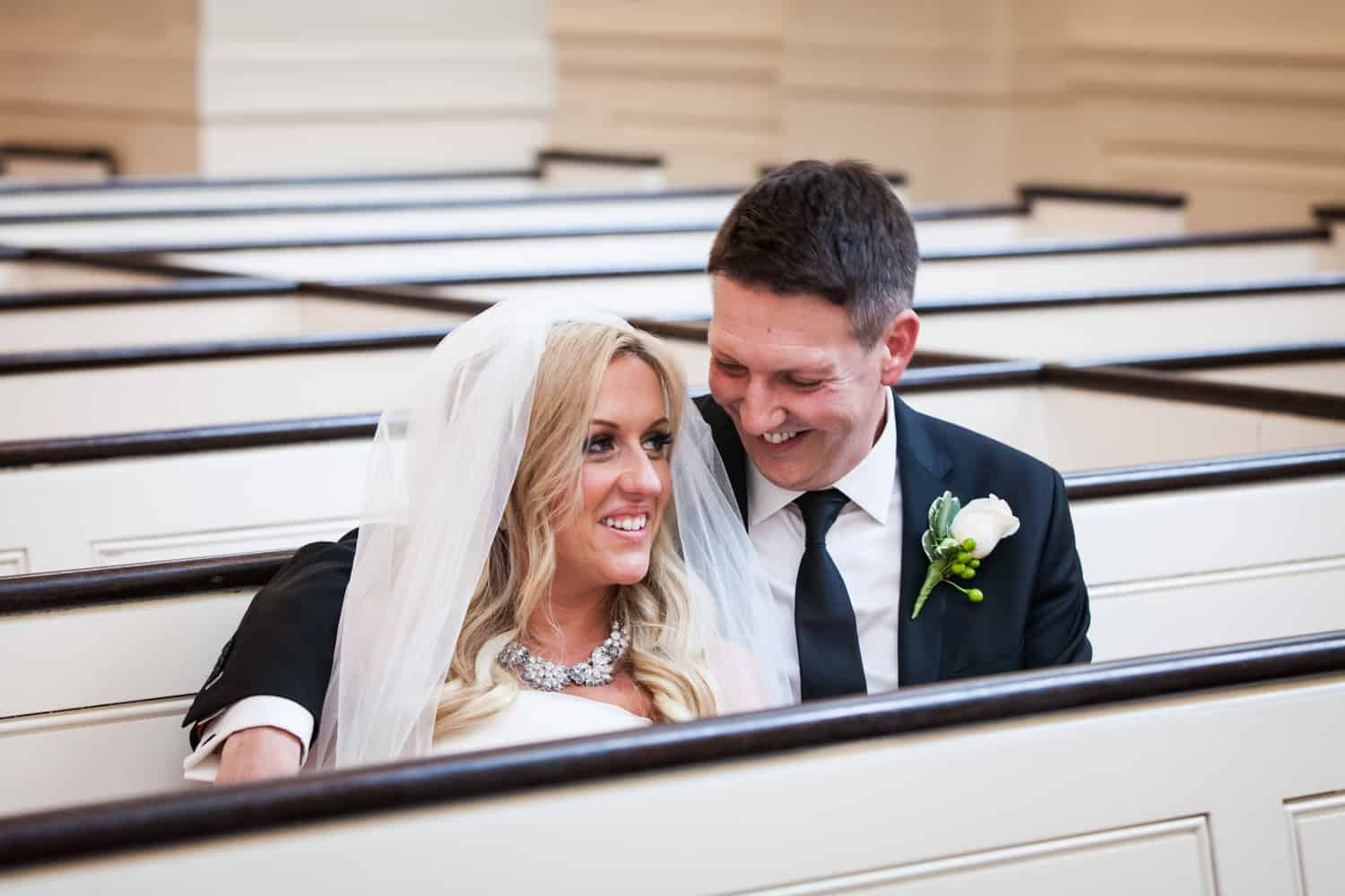 Bride and groom cuddling in pew