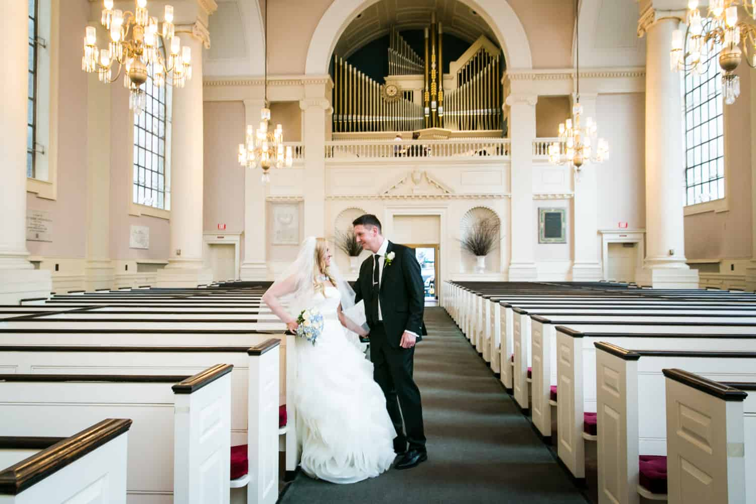 Bride and groom leaning against pews in All Souls Unitarian Church