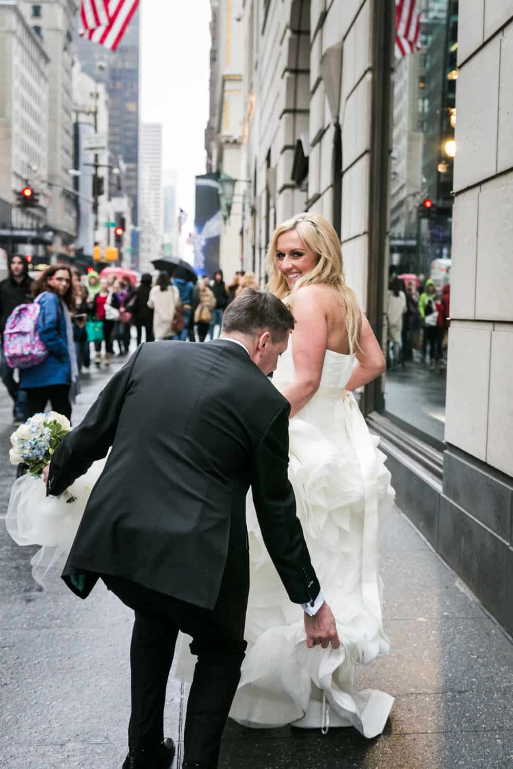 Groom helping bride with dress on NYC sidewalk