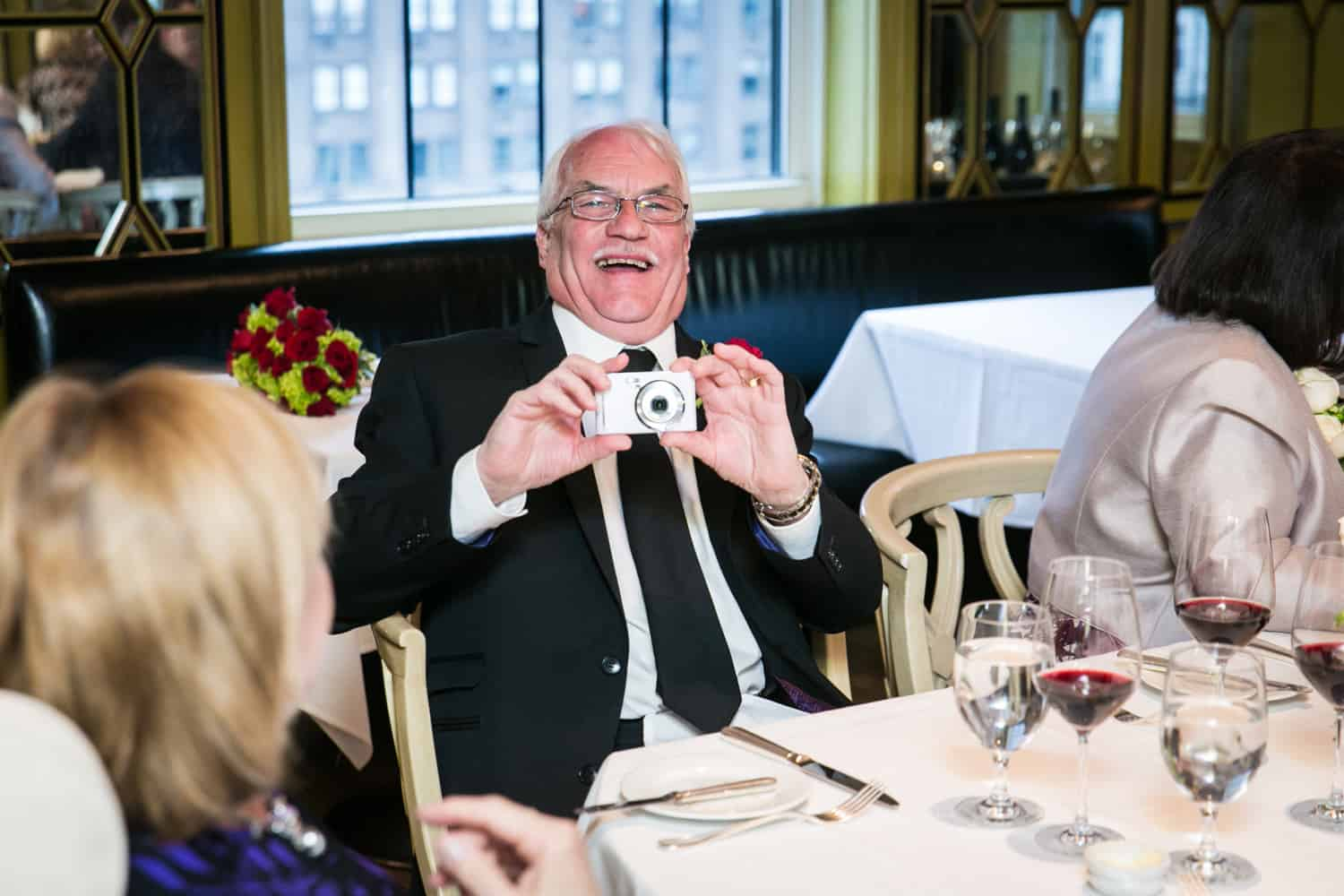 Older gentleman taking photo at a Bergdorf Goodman wedding reception