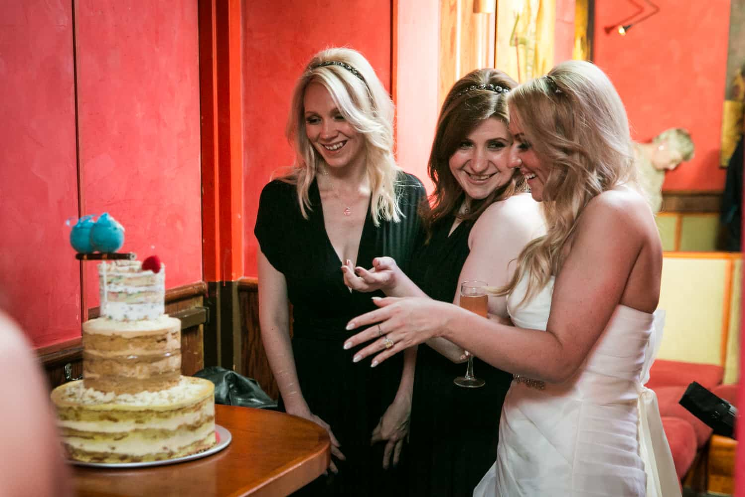 Bride showing off cake to female guests at a Bergdorf Goodman wedding reception