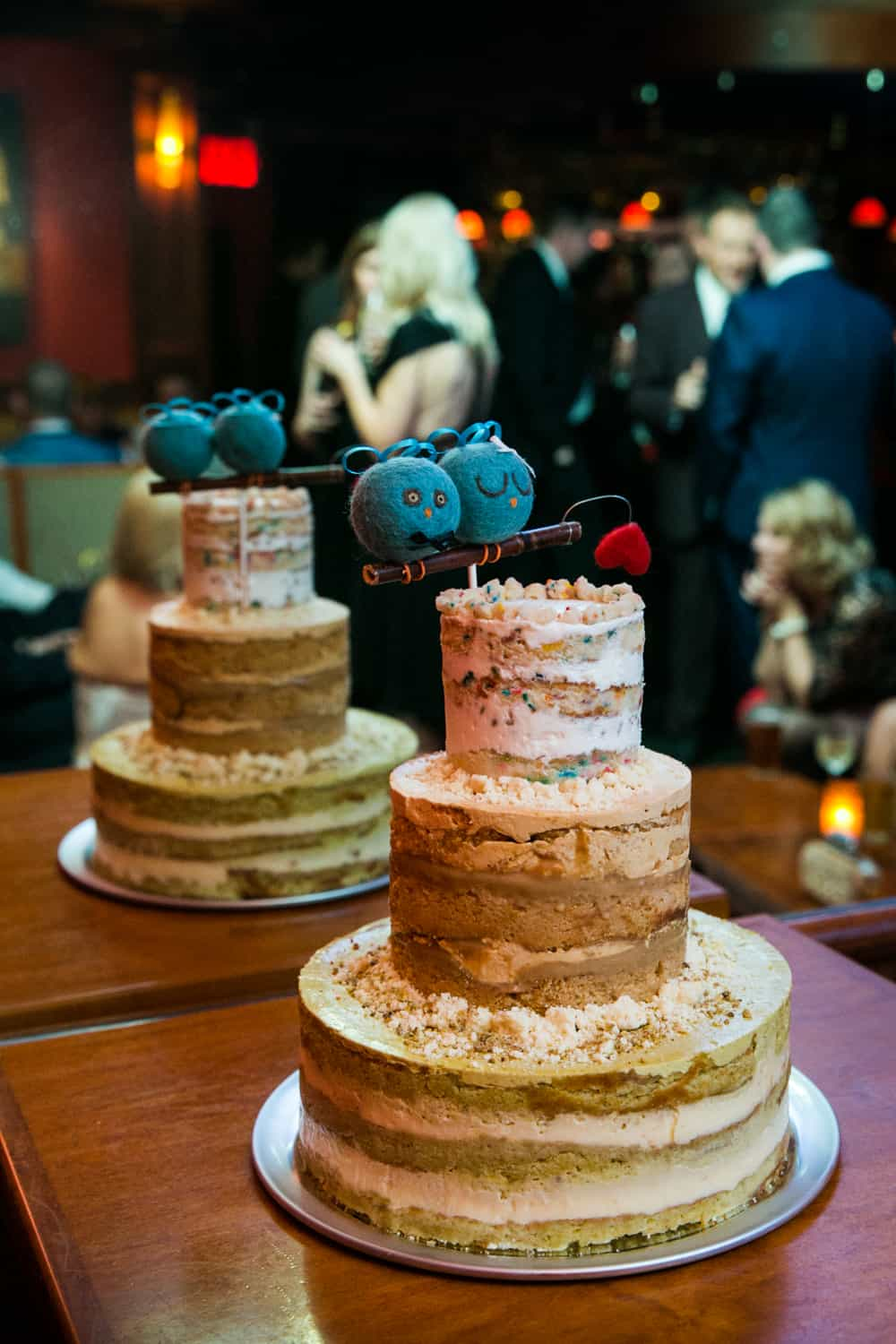 Wedding cake with blue bird topper at a Bergdorf Goodman wedding reception