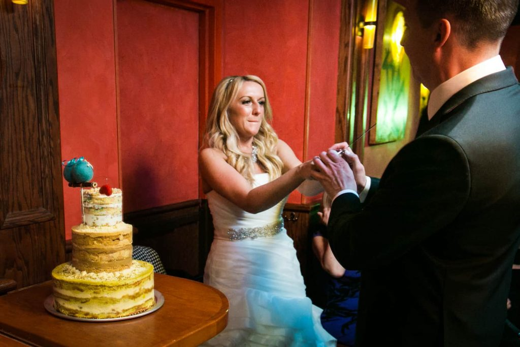 Bride pointing knife at groom with wedding cake at a Bergdorf Goodman wedding reception