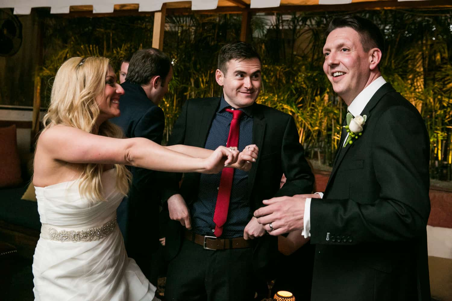 Bride dancing with groom and guest at a Bergdorf Goodman wedding reception