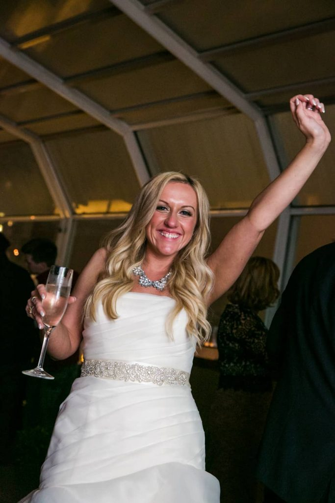 Bride dancing with hand outstretched and holding glass of champagne