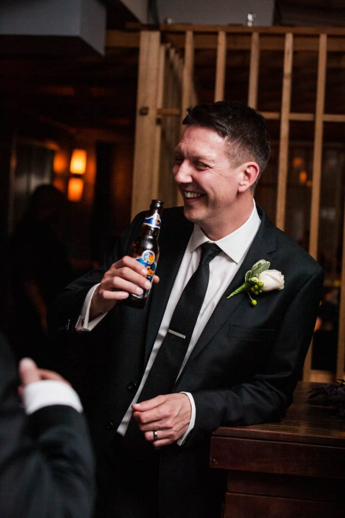 Groom drinking bottle of beer at a Bergdorf Goodman wedding reception