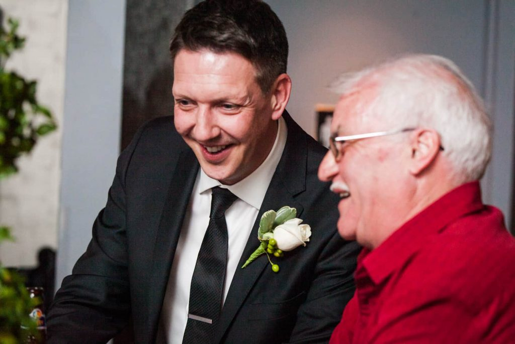 Groom laughing with older male guest