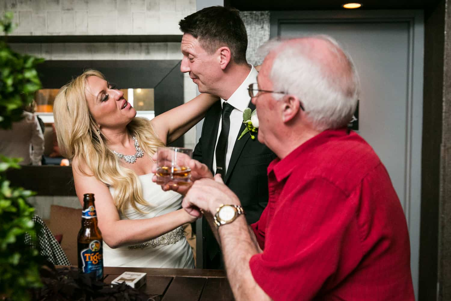 Bride and groom laughing with older male guest