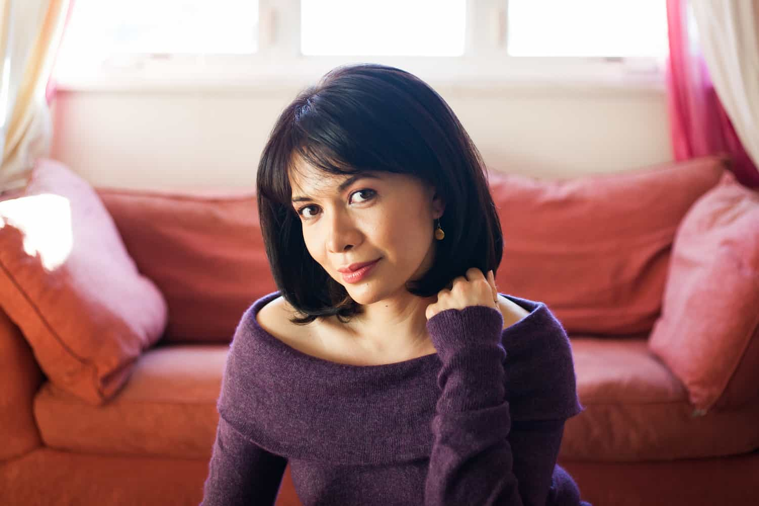 Woman with short black hair wearing purple sweater for an article on how to look slimmer in photos