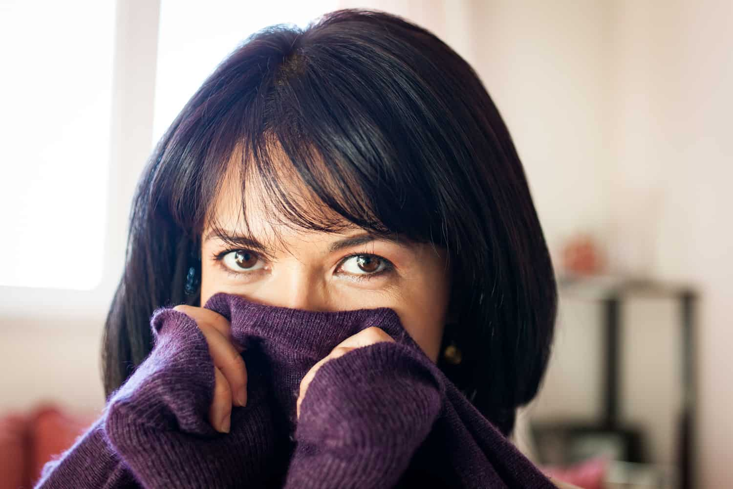 Woman with short black hair holding sweater in front of her face for an article on how to look slimmer in photos