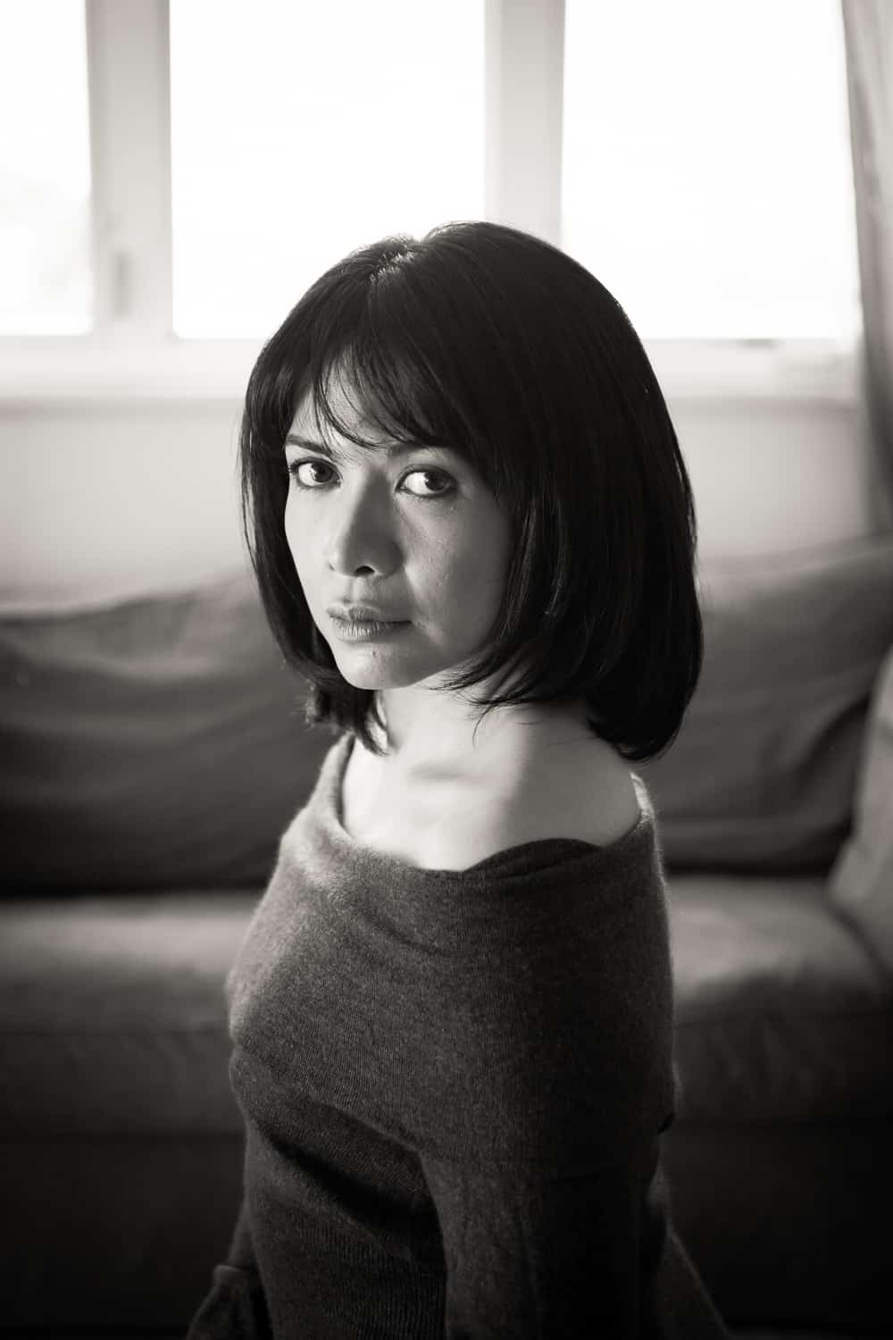 Black and white photo of woman with short black hair wearing off-shoulder sweater