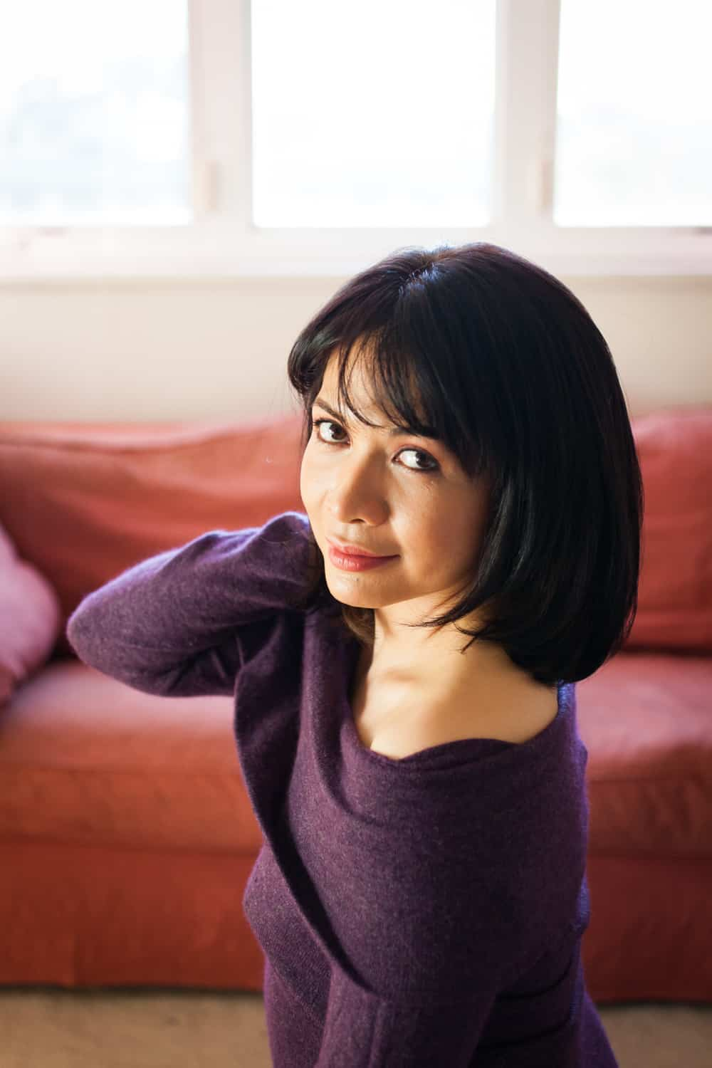 Woman with short black hair wearing purple off-shoulder sweater