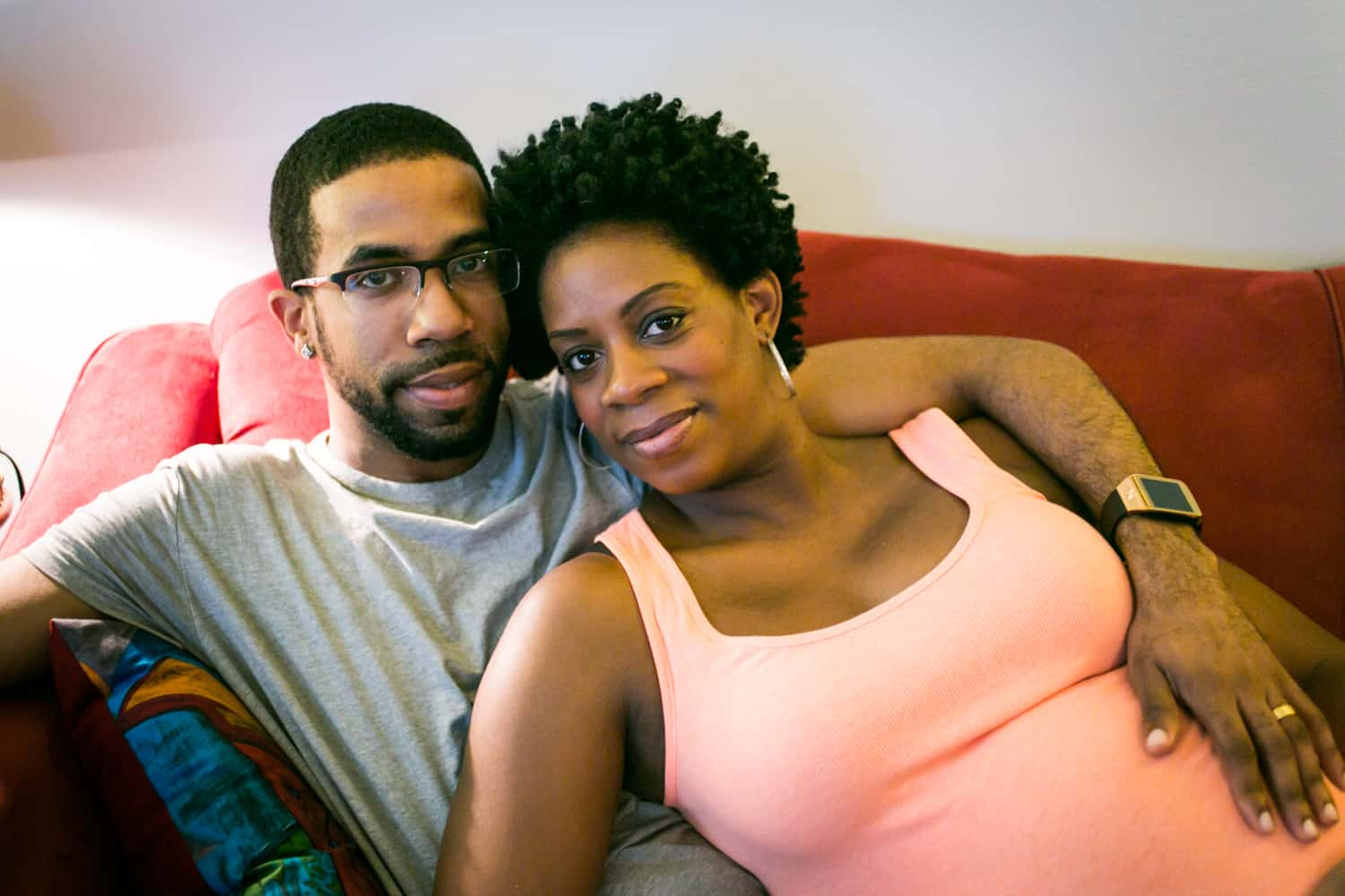 Parents-to-be sitting on couch by Queens maternity photographer