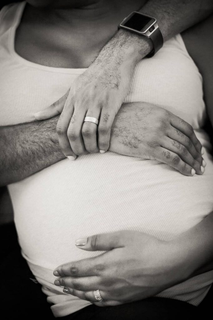 Close up of parents-to-be touching pregnant stomach by Queens maternity photographer