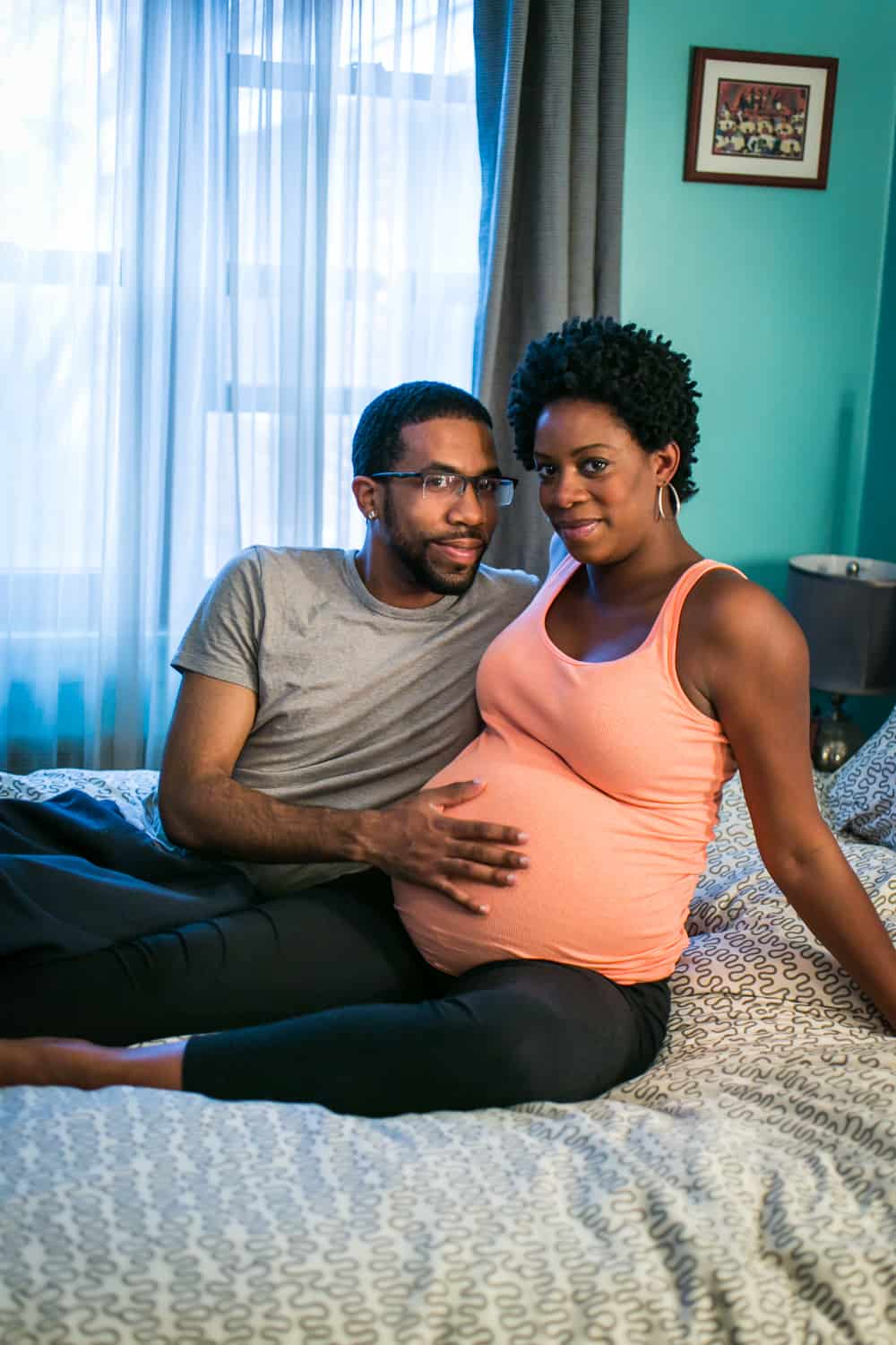 Parents-to-be sitting on bed by Queens maternity photographer