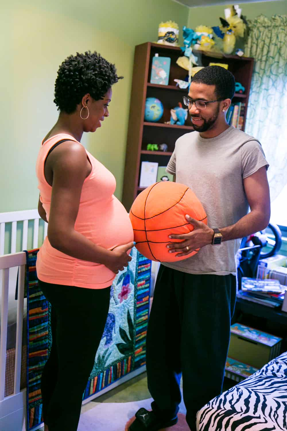 Parents-to-be comparing pregnant stomach to stuffed basketball by Queens maternity photographer