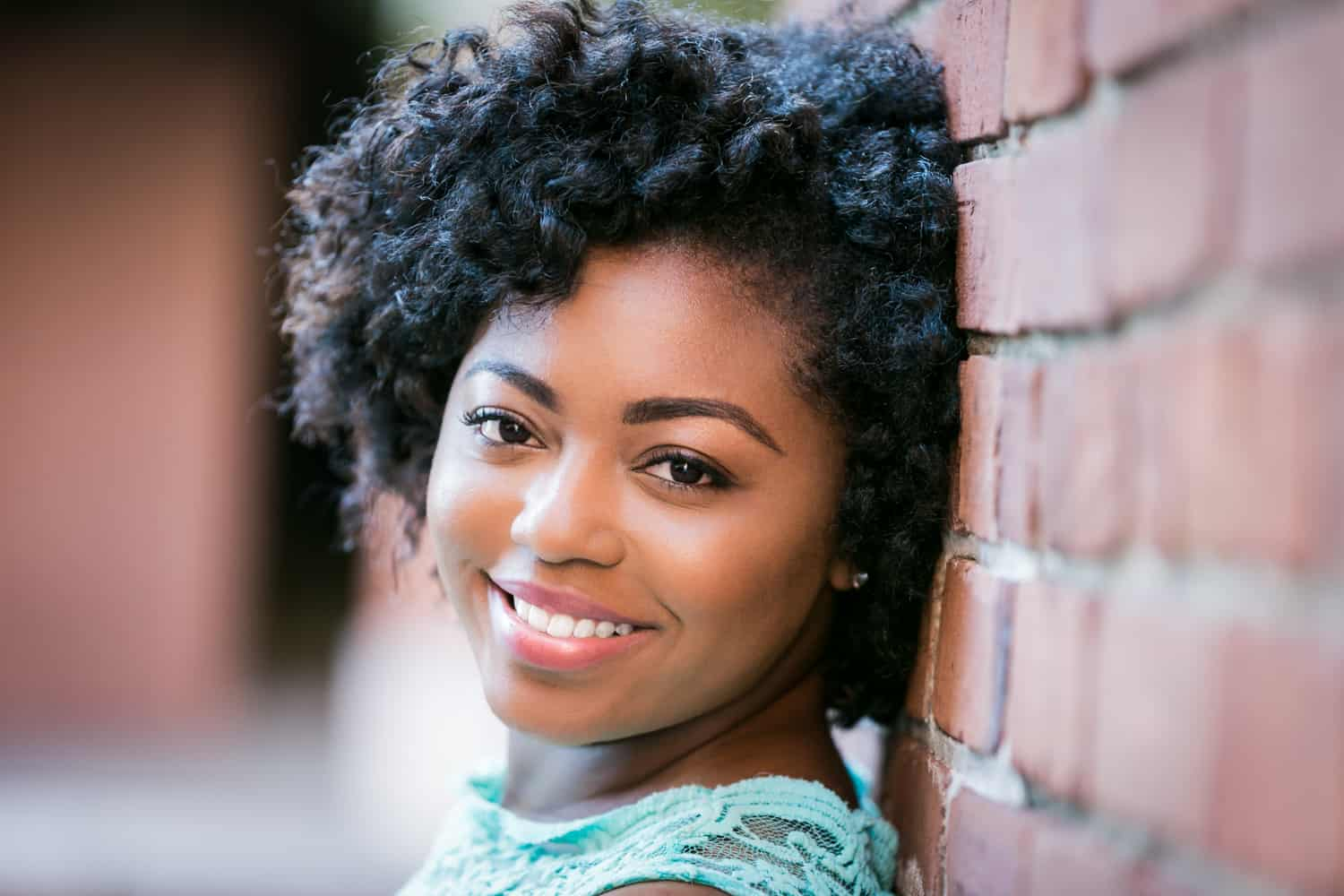 Headshot of African American model against brick wall