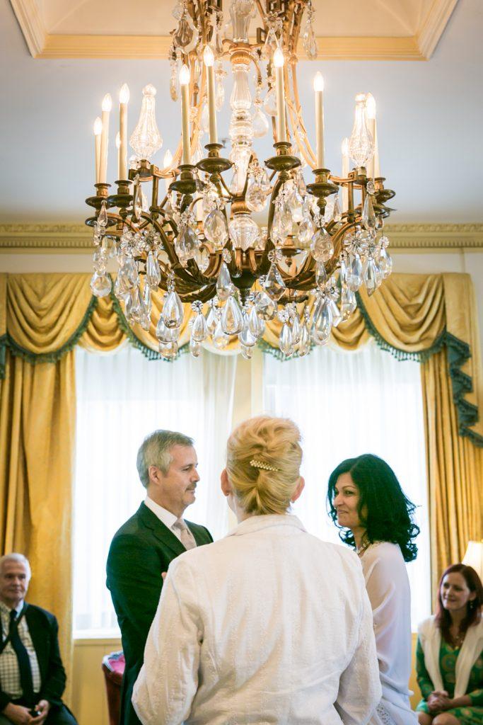 Bride and groom underneath chandelier at a Waldorf Astoria wedding