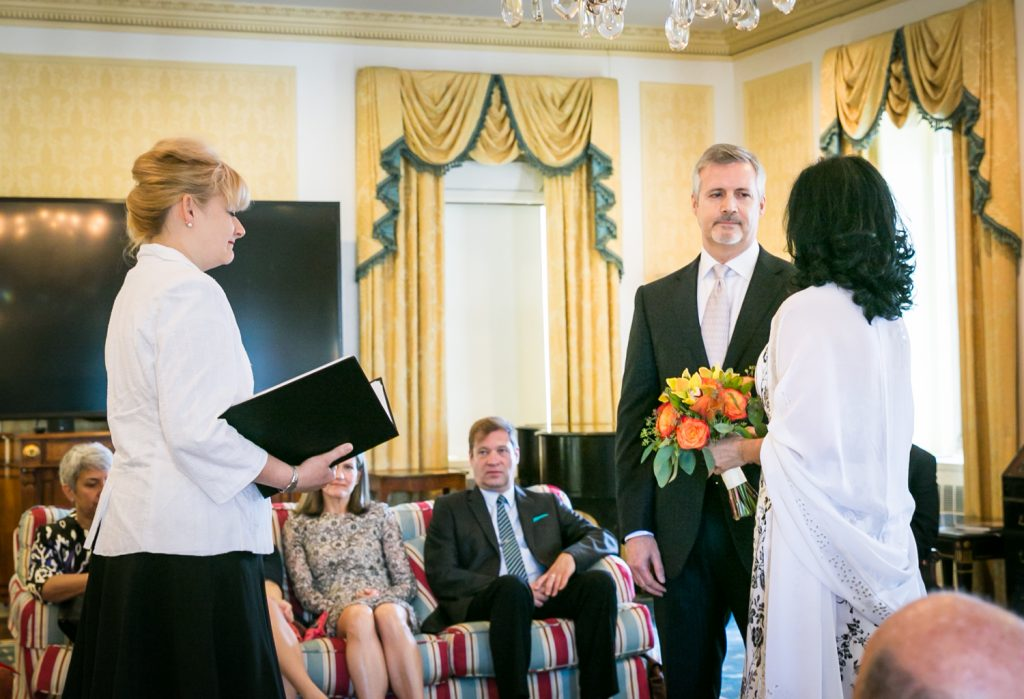 Couple exchanging vows in hotel room at a Waldorf Astoria wedding