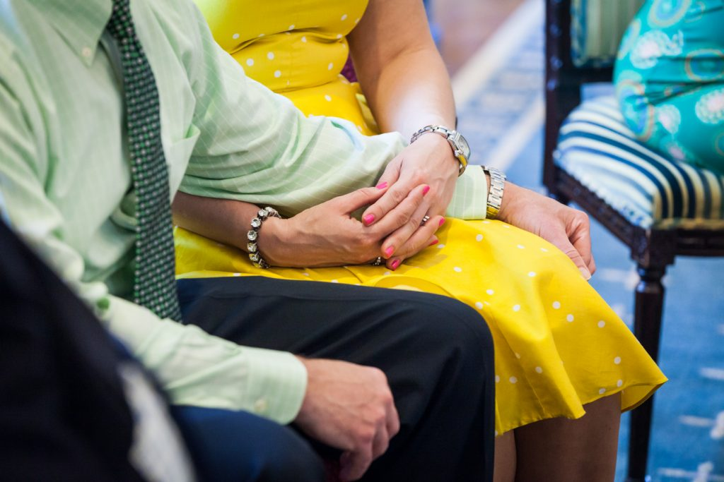 Close up on guests holding hands at a Waldorf Astoria wedding