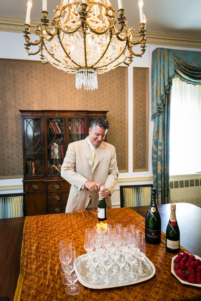Man opening bottle of champagne at a Waldorf Astoria wedding