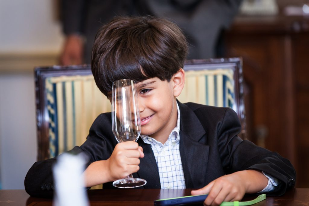 Little boy playing with champagne glass at a Waldorf Astoria wedding