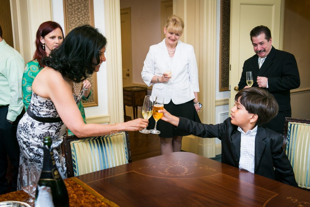 Bride toasting champagne glass with little boy