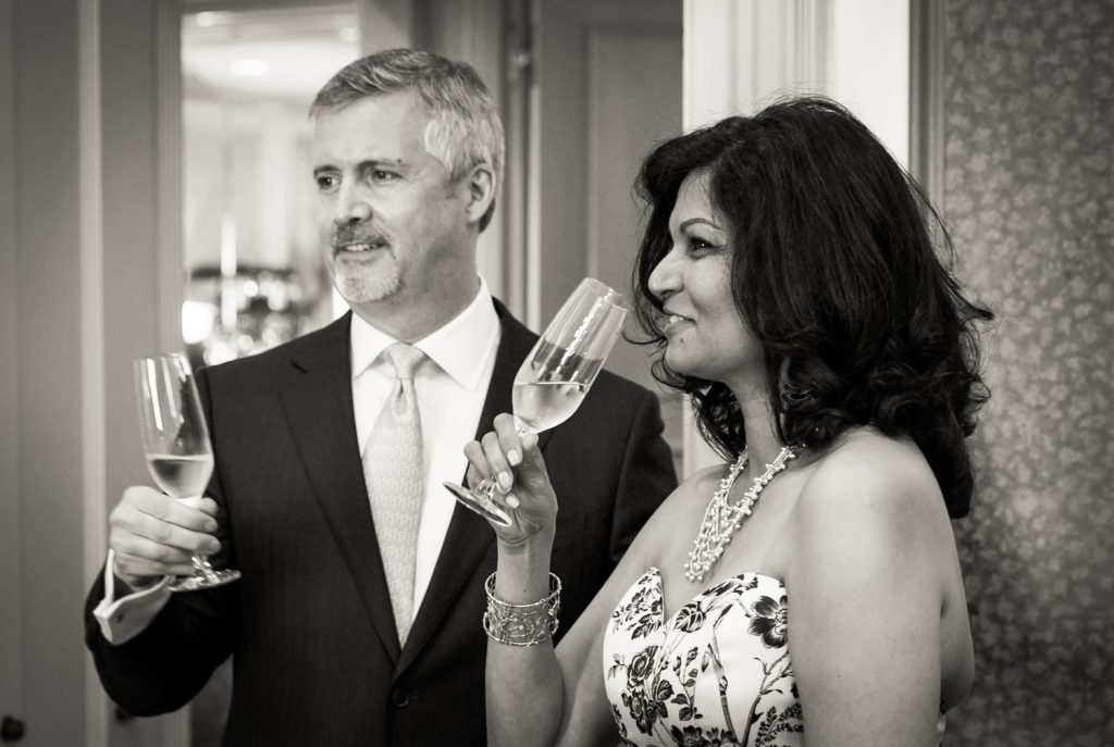 Black and white photo of bride and groom holding champagne glasses