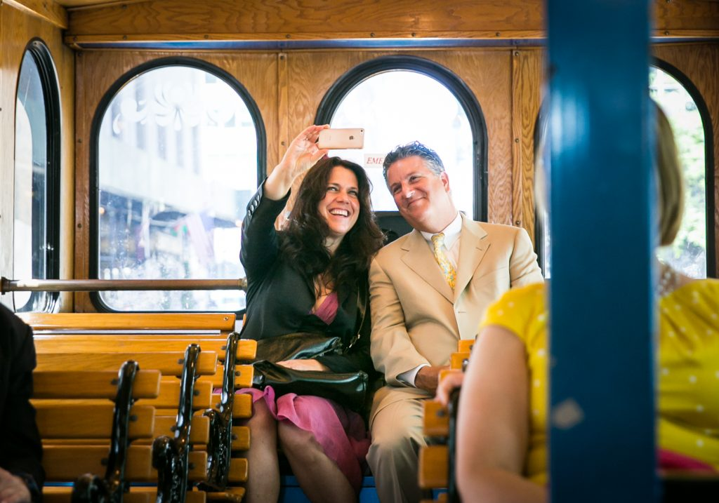 Couple taking selfie with cell phone on board trolley