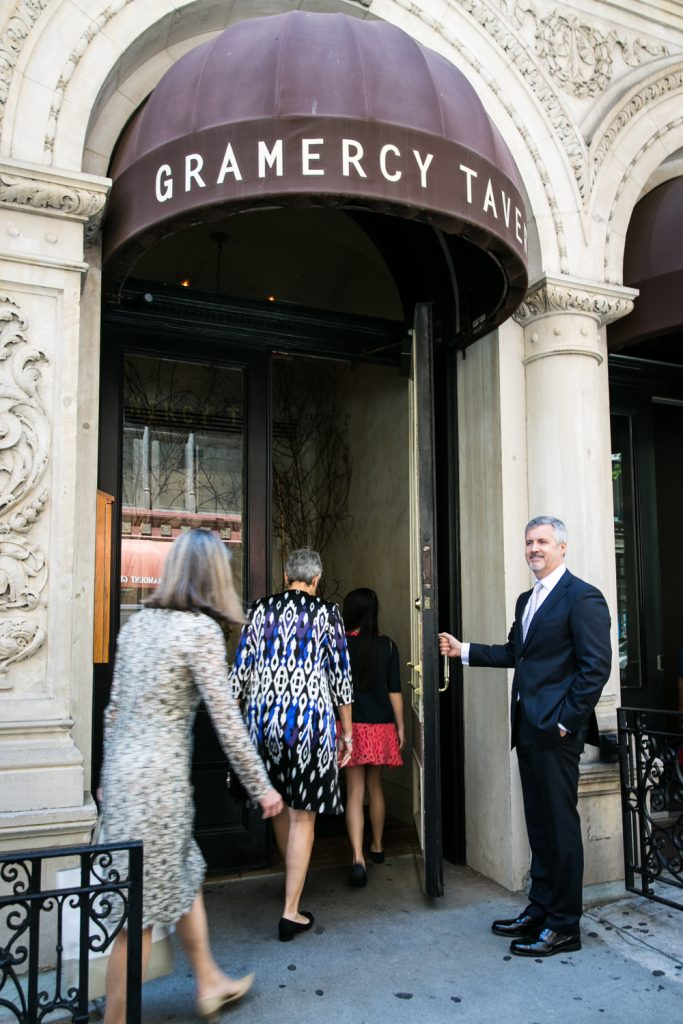Groom holding door open for guests at Gramercy Tavern