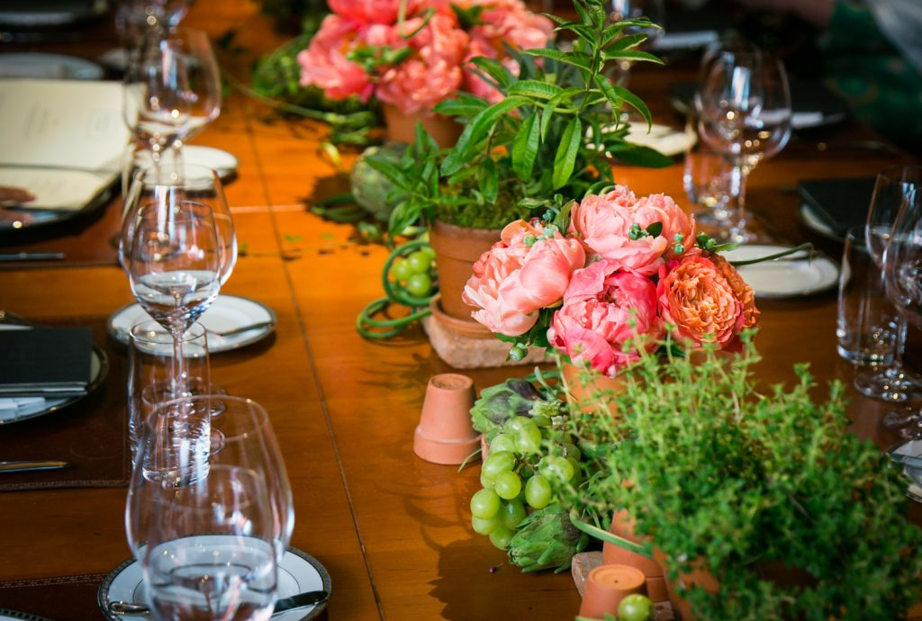 Place setting with red flowers at Gramercy Tavern wedding reception