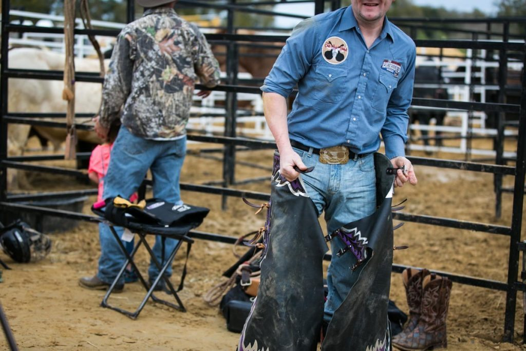 A cowboy changes out of his chaps at the county fair championship rodeo, by NYC photojournalist, Kelly Williams