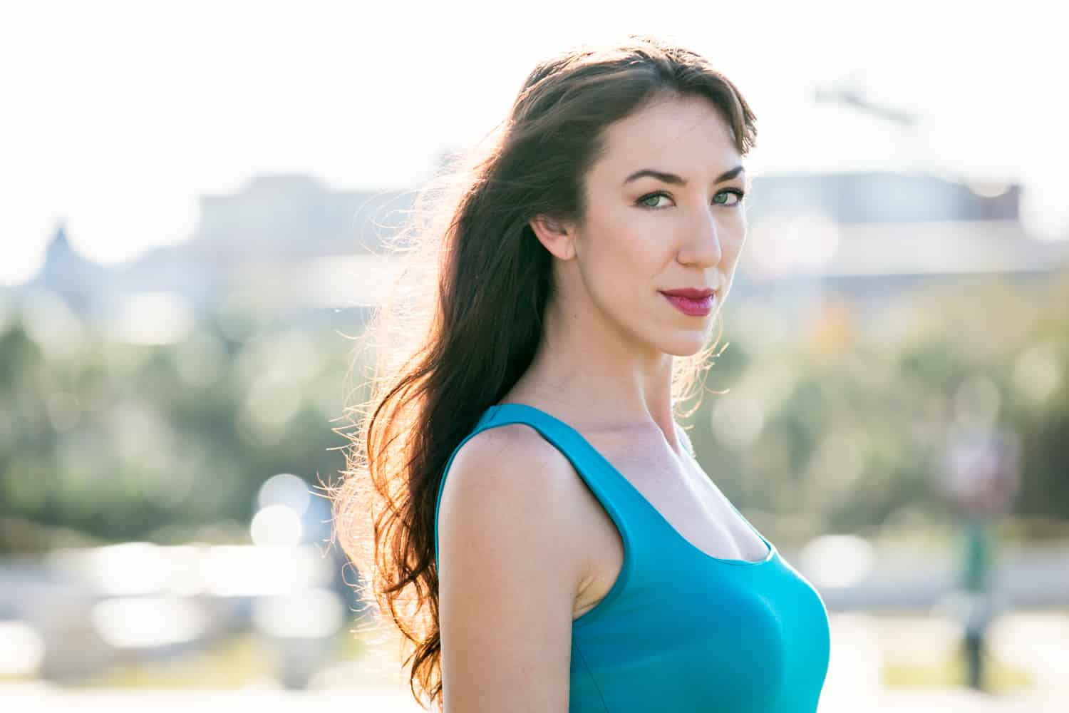 Acting headshots of model with long dark hair and blue tank top