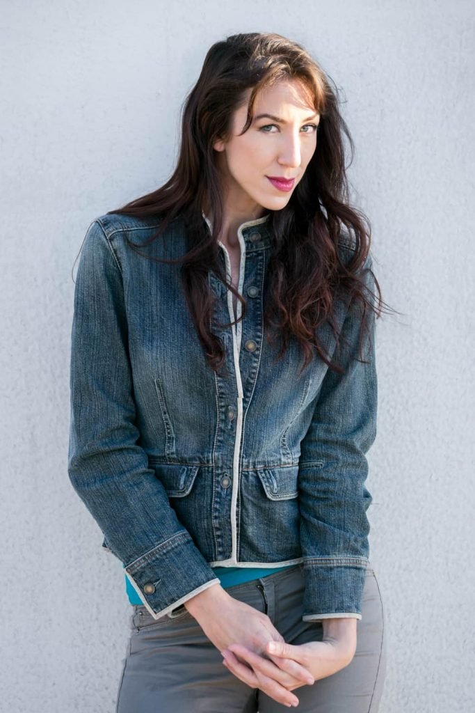 Headshot of model with long dark hair and jean jacket