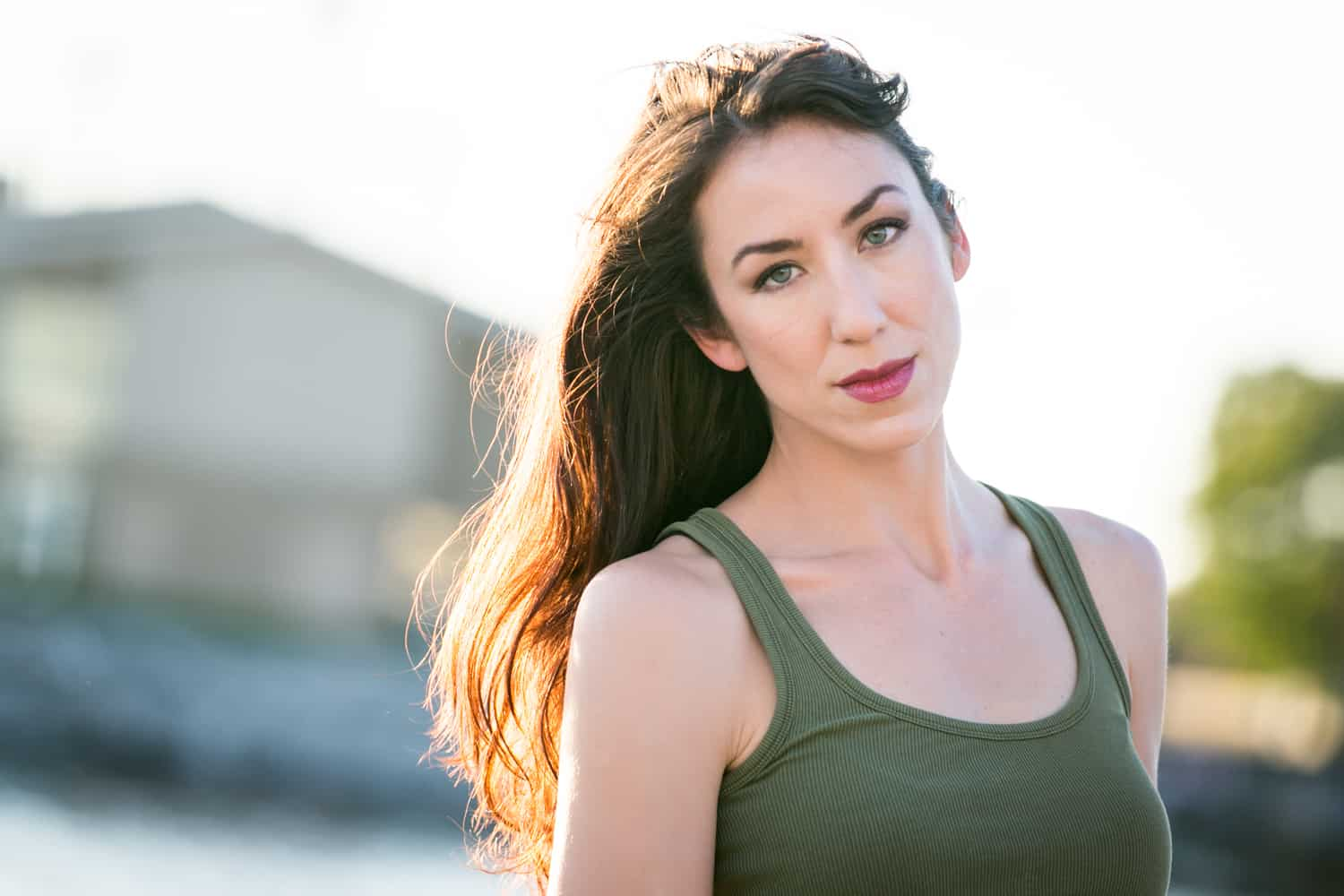 Acting headshot of model with long dark hair and olive tank top