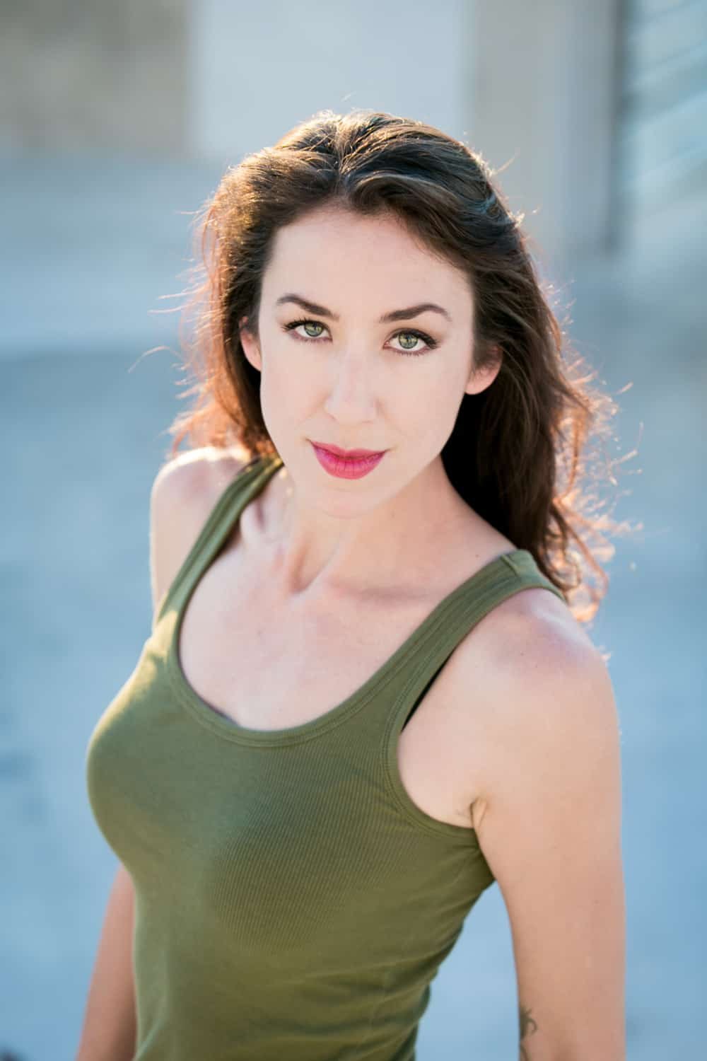 Headshot of model with long dark hair and olive tank top