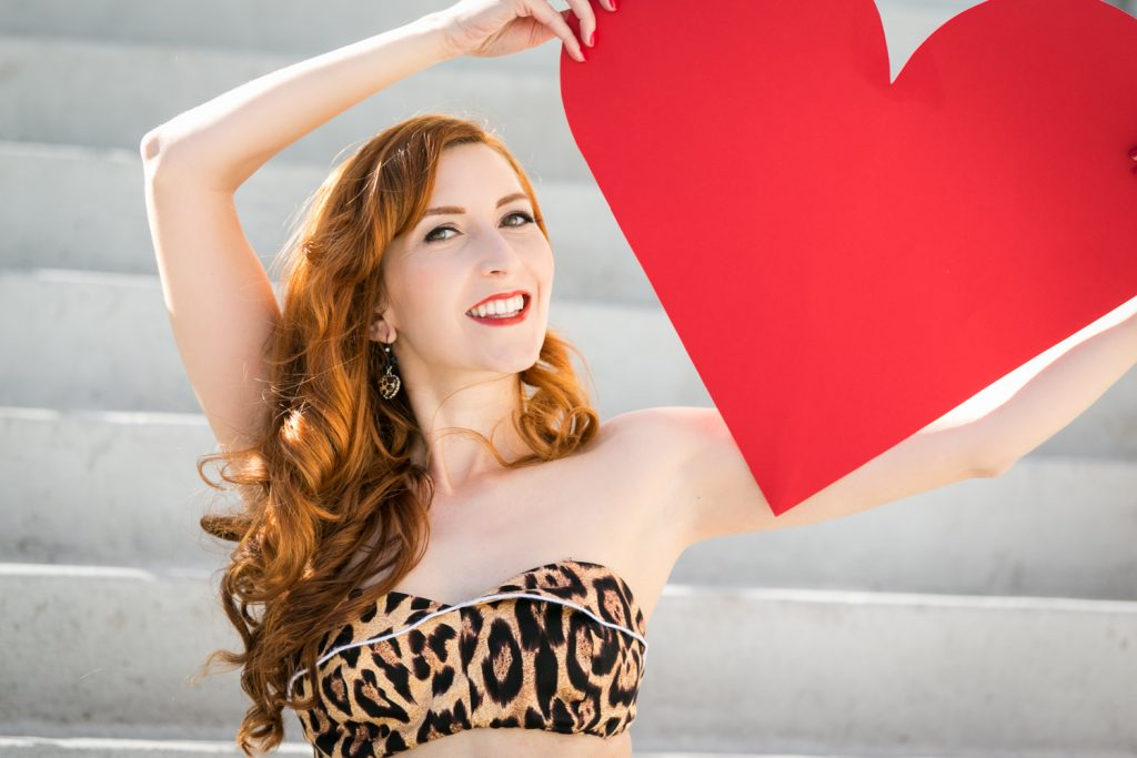 Pinup model holding red heart and wearing leopard bikini top at a pinup photography shoot
